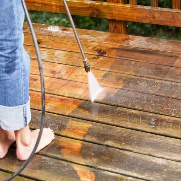 """A woman with rolled jean and bare feet s is using a  pressure washer sprayer to clean a weathered treated wood deck. The wood on the left has been cleaned, the right is weathered and dirty. Focus is on the wood, the nozzle is slightly soft."""